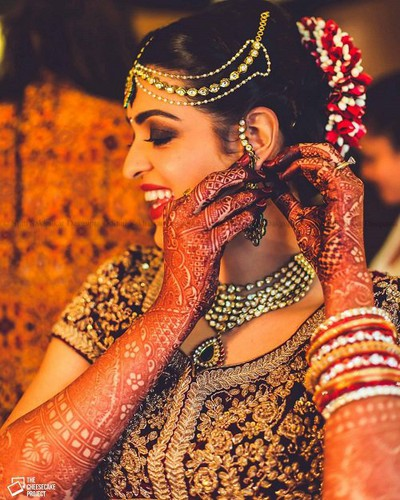 Beautiful Indian women in bridal look with Full hand mehndi, gold jewellery, floral bun hairstyles and designer blouse designs